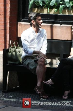Fashion designer Marc Jacobs sitting on a bench talking to a female friend New York, USA - 05.06.10