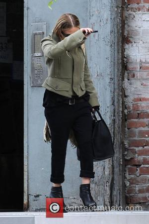 Mary-Kate Olsen covers her face from photographers as she departs her Manhattan home New York City, USA - 16.05.10