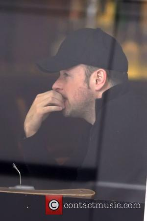 Matthew Vaughn sitting in a cafe near to the hospital where his supermodel wife recently gave birth to a baby...