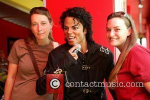 Fans posing with Michael Jackson's wax figure Madame Tussauds in Washington, D.C. installs a Michael Jackson tribute exhibit to mark...