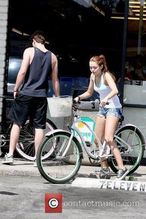 Liam Hemsworth and Miley Cyrus  Miley Cyrus rides her bicycle with her boyfriend and 'The Last Song' co-star to...