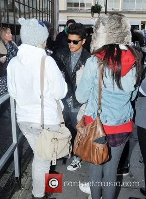 Bruno Mars signs autographs for fans  as he arrives at the BBC Radio One studios London, England - 19.01.11