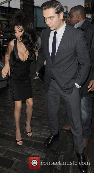 Amy Winehouse shows a bit more than she may have intended, as she arrives at the opening of Shaka Zulu...