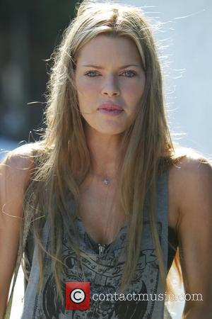 Sophie Monk with her new brown hair, carries white plastic shopping bags while shooting a scene for her new pilot...
