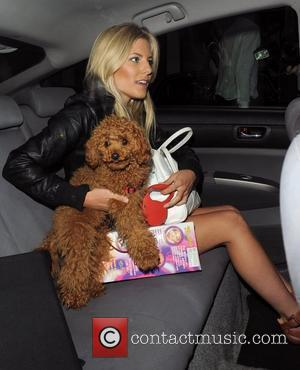 Mollie King from girl group The Saturdays leaving a office building with her pet poodle Alfie, having taken part in...
