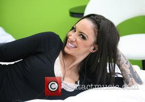Jodie Marsh poses in a giant bed before attempting to complete a record-breaking 24-hour three-way call at Victoria station London,...