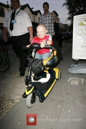 Verne Troyer sporting an Arsenal Football Club shirt with his name on the back, arrives at a west London studio...