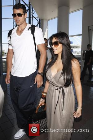 Petite Kim Kardashian is dwarfed by new husband Kris Humphries as they arrive at LAX to fly out to New...