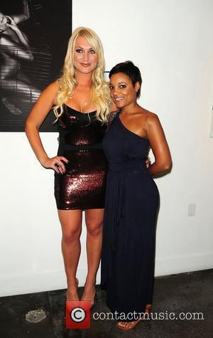 Brooke Hogan and Amaris Jones attend a portrait unveiling at the Women In Cages exhibit at Cafeina Lounge Miami, Florida...