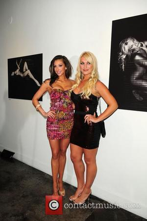 Katrina Campins and Brooke Hogan attend their portrait unveiling at the Women In Cages exhibit at Cafeina Lounge Miami, Florida...