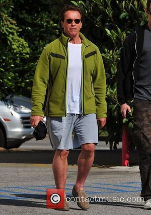 Arnold Schwarzenegger at the Brentwood Country Mart, wearing a green fleece jacket with knee-length shorts, and slip-on shoes Brentwood, California...
