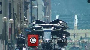 The Batplane is transported through a scene with a Batman figure in the cockpit on the set of the new...
