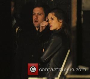 Joe Cole and Carley Cole watch from the side of the stage at Liam Gallagher of Beady Eye perform in...