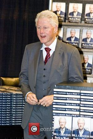 Former U.S. President Bill Clinton signs copies of Back to Work: Why We Need Smart Government for a Strong Economy...