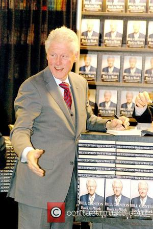 Former U.S. President Bill Clinton signs copies of his new book, 'Back to Work: Why We Need Smart Government for...
