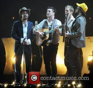Ted Dwane, Ben Lovett, Marcus Mumford and Winston Marshall of Mumford and Sons perform ,  The BRIT Awards 2011...