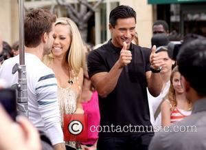 Louis Van Amstel, Kendra Wilkinson and Mario Lopez filming an interview for the entertainment television news programme 'Extra' at The...