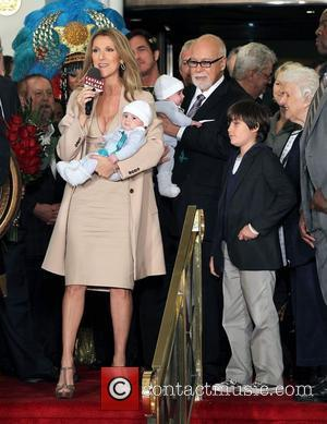 Singer Celine Dion holds her son Nelson Angelil next to her husband and manager Rene Angelil, holding their son Eddy...