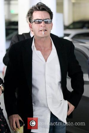 Charlie Sheen smoking a cigarette as he leaves an office building in Beverly Hills with his girlfriend Los Angeles, California...