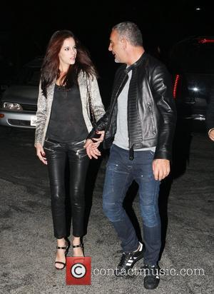 Christian Audigier takes his girlfriend Nathalie Sorensen for a celebratory dinner after a deal was finalised between the fashion designer's...