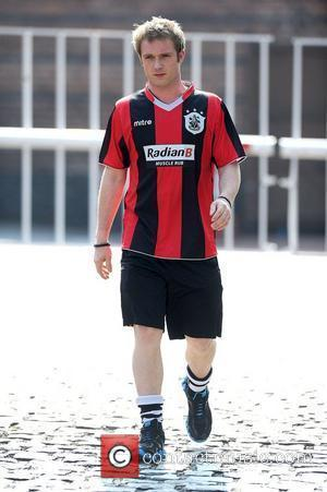 Chris Fountain leaves Granada Studios from filming 'Coronation Street' to go jogging in his Hudderfield Town football shirt. Manchester, England...
