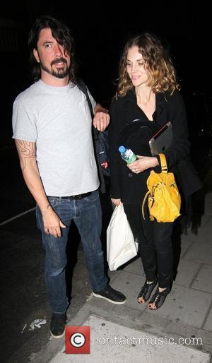 Dave Grohl and his wife Jordyn Blum arrive at their London hotel at 2am London, England - 04.07.11