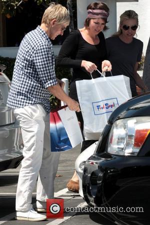 Ellen DeGeneres and Portia de Rossi Ellen DeGeneres struggles to get her the front of her car opened as she...