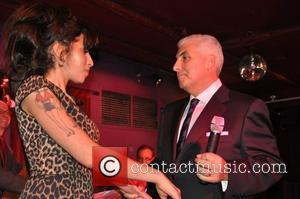 Amy Winehouse runs on to the stage as her father Mitch Winehouse is performing. After Amy tries to tell the...