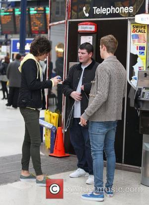 Frankie Cocozza arrives at Brighton train station to head to London. Frankie chatted to friends while queuing to buy a...