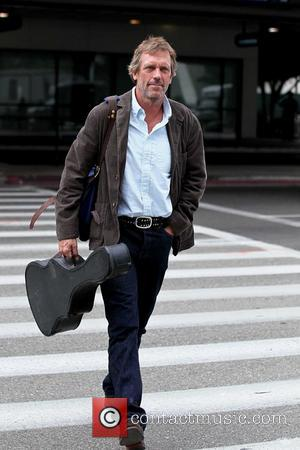 Hugh Laurie carrying his guitar as he arrives at LAX airport on a flight from London Los Angeles, California -...