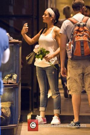 Jenni Farley aka JWoww spraying perfume 'Jersey Shore ' cast member holding flowers that were delivered to her Florence residence...