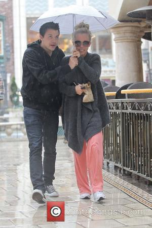 Kendra Wilkinson and male companion go shopping together at The Grove, sheltering under an umbrella in the rain. Los Angeles,...