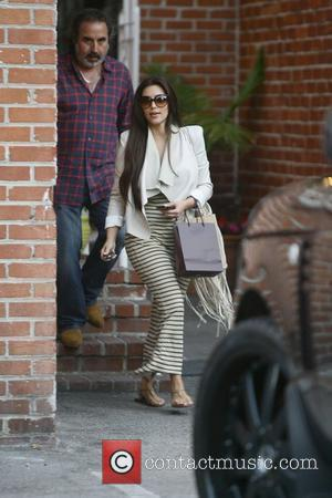 Kim Kardashian, wearing a white blazer and striped maxi dress, is seen leaving a beauty salon in West Hollywood West...