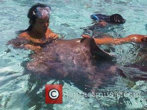 Kimora Lee Simmons  swimming with sharks while on holiday in Bora Bora. Simmons tweeted: I swam w wild sharks...