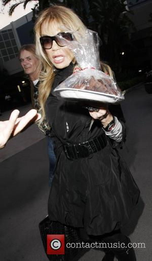 Dyan Cannon holding brownies  as she arrives at the Staples Center for the Lakers game  Los Angeles, California...