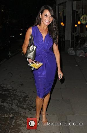 Lizzie Cundy is all smiles as she is spotted walking in Mayfair with her sons, Josh and James, who were...