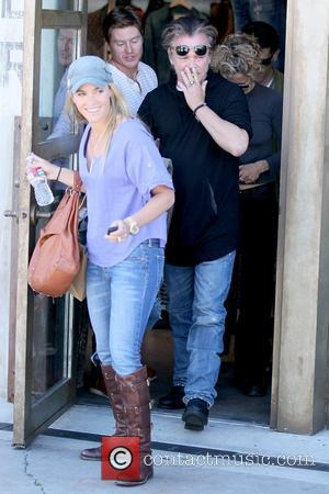 John Mellencamp and Meg Ryan (in background) Meg Ryan leaving RRL boutique in West Hollywood after shopping with her boyfriend...