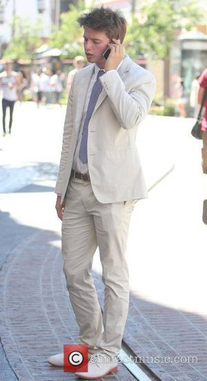 Patrick Schwarzenegger wearing a white suit and shoes takes a break while working at the Grove as an intern. Hollywood,...