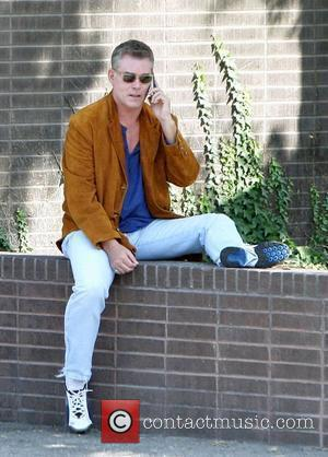 Ray Liotta dressed casually in a brown suede jacket and light blue jeans talks on his iPhone while out and...