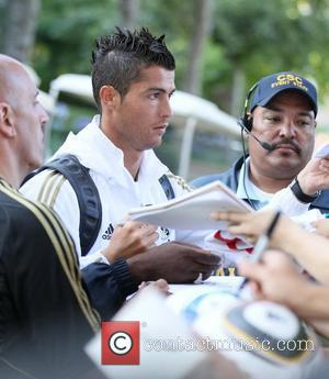 Real Madrid forward Cristiano Ronaldo signs autographs for fans as he leaves a training session with the rest of his...