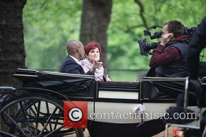 Sharon Osbourne is interviewed while sitting on a horse drawn carriage along the route the procession of the royal wedding...