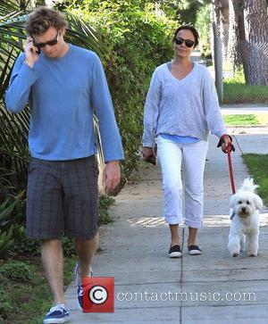 Simon Baker talking on his cellphone with his wife Rebecca Rigg walking their dog in Santa Monica. Santa Monica, California...