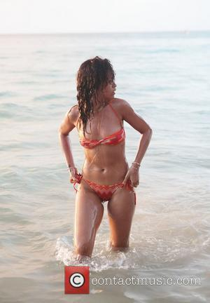 Rihanna walks back to the beach after swimming in the sea wearing a skimpy orange bikini The sexy singer is...