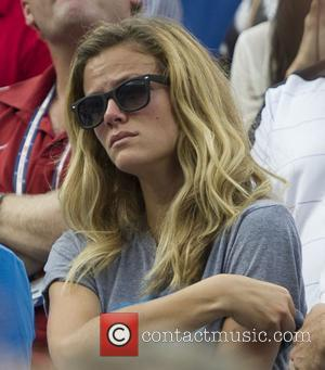 Brooklyn Decker watches Andy Roddick (USA) lose to Juan Martin Del Potro of Argentina after their men's singles fourth round...