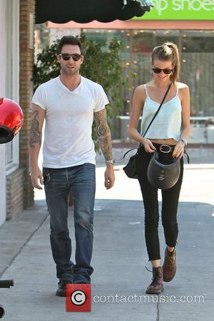 Adam Levine and girlfriend Behati Prinsloo  returns to his parked motorcycle after having lunch at Mustard Seed Cafe in...