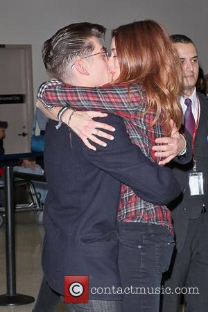 Arctic Monkeys star Alex Turner engages in a very public display of affection with a beautiful redhead as he arrives...
