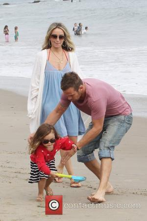 Cam Gigandet and his wife Dominique Geisendorff walk with their daughter Everleigh Ray Gigandet on the beach in Malibu on...