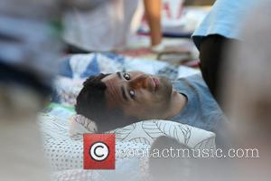 Cliff Curtis  seen laying down at the Grove. Cliff also carries two boxes of pizza Los Angeles, California -...