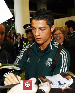Cristiano Ronaldo is mobbed by fans as he arrives at Manchester Airport ahead of Real Madrid's match against Manchester Cit...