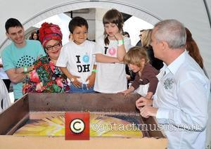 Damien Hirst and Camilla Batmanghelidjh  supervising local school children to create a spin painting at Covent Garden. London, England...